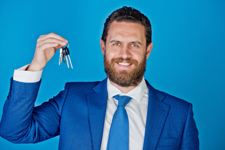 classy house: keys in hand of happy smiling businessman on blue background