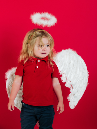 angel. adorable little angel boy with white feather wings and halo, crying kid with sad face and blonde hair on red background, cupid on valentines day holiday Stock Photo - 78342305