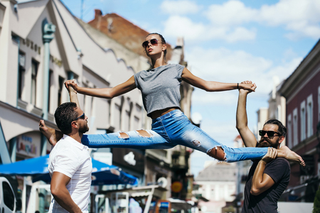 leg split of young woman in street training sport in city outdoor on hands of men Stock Photo