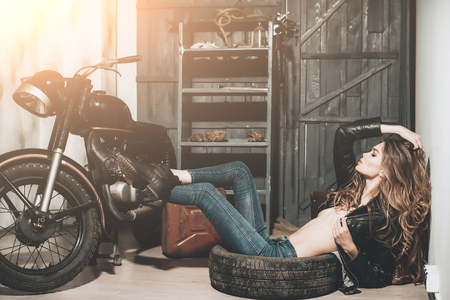 garage. Sexy woman or pretty girl, stylish model with blond, curly, long hair in erotic unbutton, leather jacket lying in dirty, rubber tire on floor on motorcycle garage background. Wheel and vehicle service
