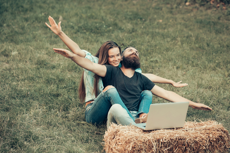 Happy couple in love of girl with long hair and bearded man, with flying gesture using laptop on hay bale on green grass on summer natural background. Technology, nature. Freedom