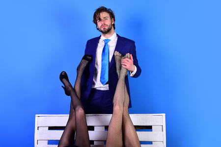 handsome man or businessman in suit and female sexy legs in fashionable shoes and tights on white wooden bench on blue background, love and relations, power, boss, office romance, sexual services