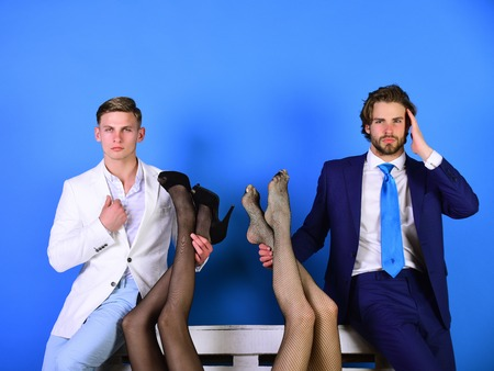 fashion and business, handsome men in suit holding female legs in fashionable shoes and tights, luxury and patriarchy