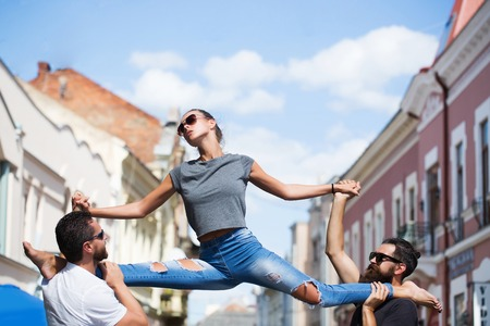 woman or sexy girl, stylish model, in sunglasses and blue jeans sitting leg split on shoulders of two caucasian, bearded men on sunny, summer day on city street. Active lifestyle, friends Stock Photo