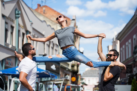 beautiful fitness sport woman or young girl in jeans making split leg on hand of handsome men outdoor
