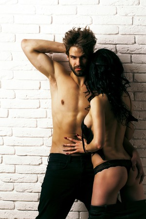Sexy couple of lovers embraces. Pretty girl or beautiful woman with buttocks, cute ass, in gstring panties and handsome man or muscular macho with long stylish hair on white brick wall