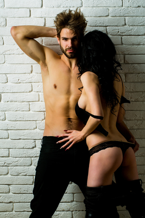 gstring: Sexy couple of lovers embraces. Pretty girl or beautiful woman with buttocks, cute ass, in gstring panties and handsome man or muscular macho with long stylish hair on white brick wall