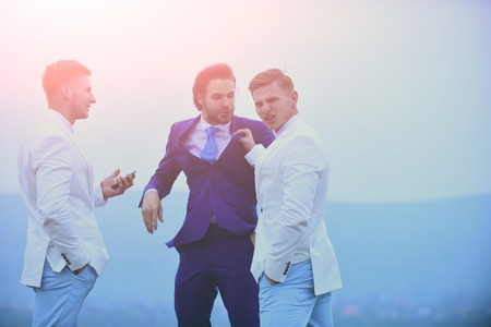 communication, group of business people in formal outfit fighting on blue sky background, businessman and twin men with phone outdoor, business conflict, conflict of interest, pressure, raidership