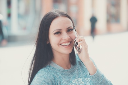 happy brunette girl speaking on mobile or cell phone with long hair and smiling pretty face outdoor