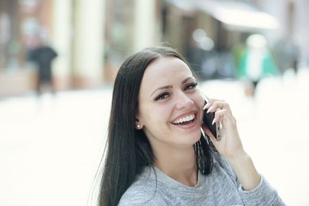 girl speaking on mobile or cell phone with long brunette hair and smiling happy pretty face outdoor Stock Photo