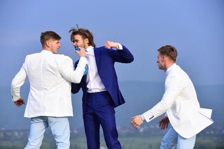 パンチ、ビジネスマンは青い空を背景に会議中に正式な衣装の男性をツインの同僚を押す