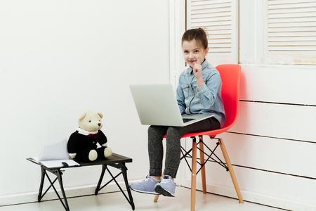 Klein meisje werk op laptop teddy beer zitten op computer tafel