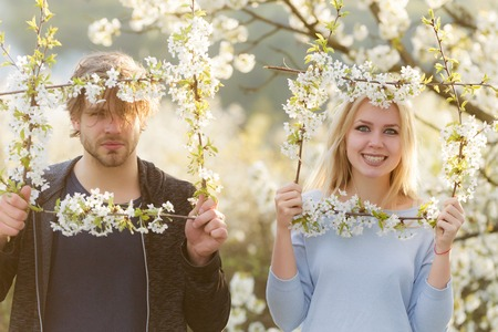 couple in love, smiling woman or cute girl with pretty smile and handsome man posing in frame of blossoming flowers on spring, sunny day on blurred floral environment. Blooming relationship