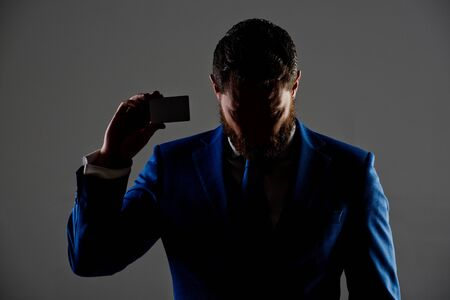 shady business. ceo or man with business or credit card in blue formal outfit in shadow on grey background, copy space, business ethics, shady business Фото со стока