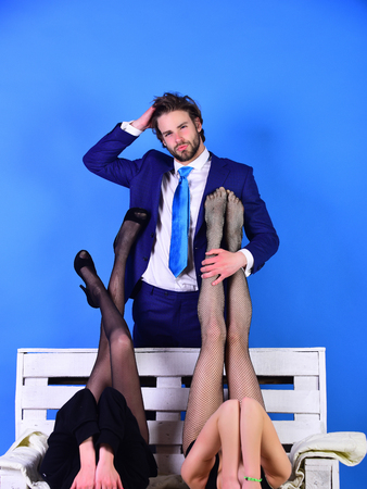 seduction and slavery. man or businessman in suit and sexy legs or woman, girl in fashionable shoes and tights on white wooden bench on blue background, love and relations, power, boss, office romance, sexual services