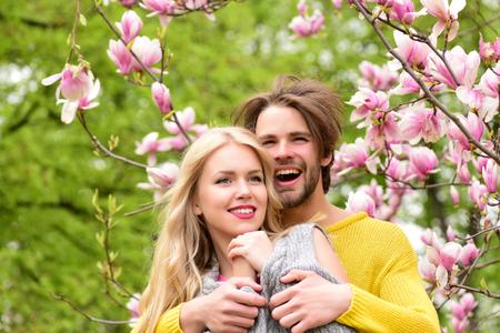 꽃이 만발한 목련 아래 나뭇 가지와 푸른 잔디, 사랑에 행복 한 커플에서 봄 정원에서 아름 다운 신혼 부부의 낭만적 인 순간