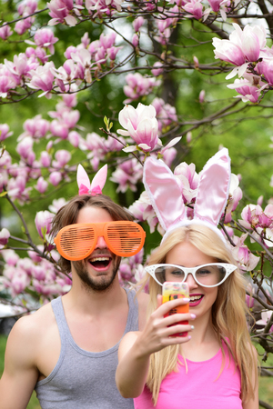 lapin sexy: Happy couple in love making selfie on smartphone at blossoming magnolia trees. Pretty girl or cute woman and handsome man smiling in funny glasses and bunny ears on floral environment. Spring. Easter