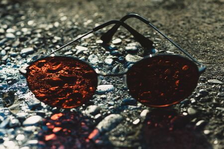 sunglasses with brown lenses and metallic spectacle frame on rough textured surface on asphalt, grey background. Protective eyewear and fashion. Vision Stock Photo