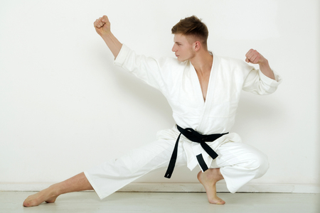 fighter, strong karate , man or athlete, posing in low fighting stance barefoot in kimono, suit, with black belt on white wall. Martial art and energy