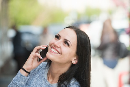woman speaking on mobile or cell phone with long brunette hair and smiling happy pretty face outdoor Stock Photo