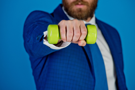 barbell in hand of businessman or bearded man in formal outfit of tie, shirt and jacket on blue background, business success Stok Fotoğraf