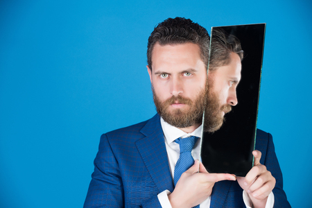 businessman or bearded serious man reflecting in mirror in outfit on blue background, multifaceted business, agile business, success and vision, barbershop and hair, copy space Stock Photo