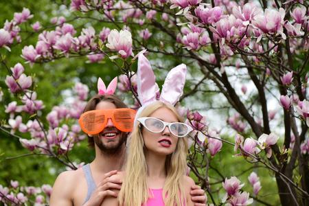 lapin sexy: L'homme ou le mâle qui se cache une fille en colère ou une belle femme sur un environnement floral. Un couple drôle, une petite amie et un petit ami dans des lunettes et des oreilles de lapin, dans un jardin de magnolia en plein essor. Printemps. Pâques