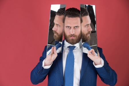 specular: man or bearded serious businessman reflecting in mirror in blue outfit on red background, multifaceted business, agile business, success and vision, barbershop and hair, copy space