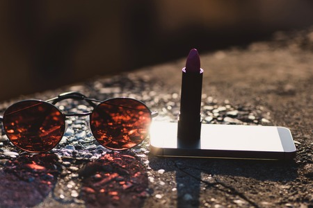 Mobile phone or smartphone with light reflection. Fashion sunglasses with brown lenses. Violet lipstick in tube. Set of accessories on asphalt surface on grey background. Cosmetic. Technology