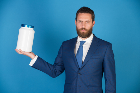 businessman or bearded man with plastic jar in formal outfit on blue background, copy space, moneybox, vitamin and drug