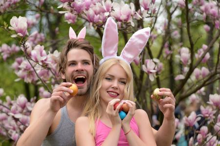 lapin sexy: Couple d'heureux homme et fille, amis de Pâques avec des ?ufs et des oreilles de lapin, jardin de magnolia de printemps