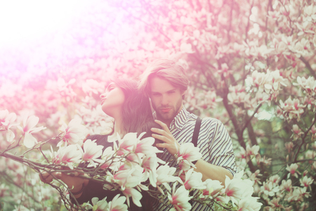 couple in love, man and pretty girl or cute woman enjoying pink, magnolia flower blossom on trees in flowering, spring park on idyllic, sunny day on blurred floral environment. Daydreaming
