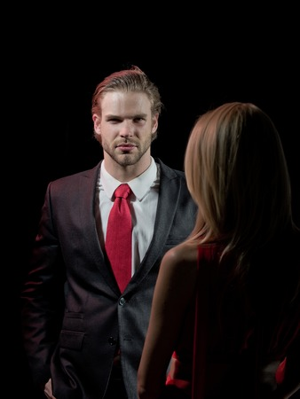 elegant couple in love of handsome man or businessman in outfit and tie with pretty blonde woman in red dress on black background