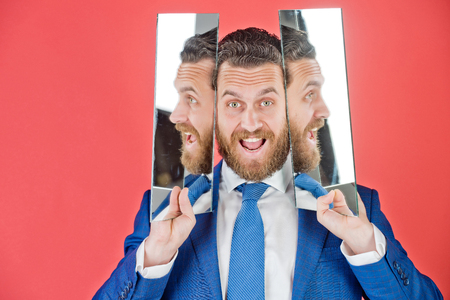 happy face of bearded hipster man or businessman reflecting in mirror in blue outfit on red background, multifaceted business, agile business, success and vision, barbershop and hair Stock Photo