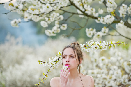 girl or sexy woman holding white, blossoming flowers in mouth and hair with naked shoulders in spring garden on sunny day on blurred floral environment. Youth and natural beauty