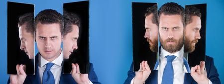 specular: man or serious businessman reflecting in mirror on blue background. Bearded or clean shaven face. Facial hair trend. Skin care. Choice, decision, agile business, archaism Stock Photo