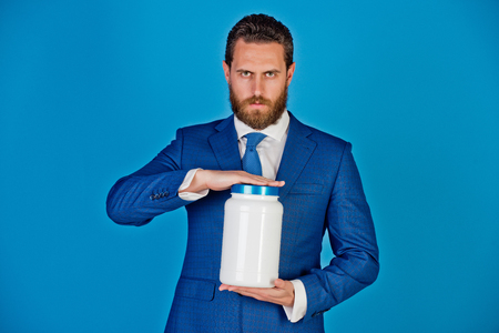 man or bearded businessman with plastic jar in formal outfit on blue background, copy space, moneybox, vitamin and drug Stock Photo