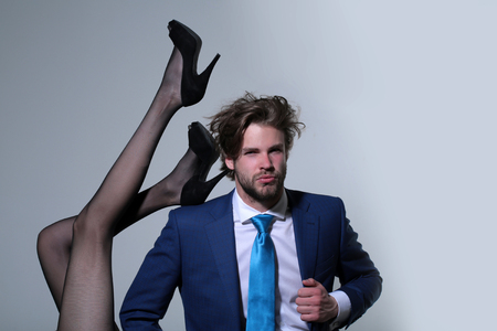 handsome man or businessman in suit and female sexy legs in fashionable shoes and tights on grey background, love and relations, power, boss, office romance, sexual services, couple in love Stock fotó