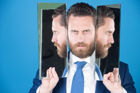 business man with beard, wearing suit, tie, holding mirror with face reflection, concept of self assured, self esteem, self checking on blue background
