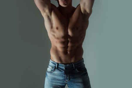 six packs, abs, on strong, naked, muscular, athletic torso, chest, arms with biceps, triceps in blue jeans on grey background. Sport and bodybuilding Stock Photo