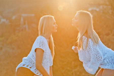 lesbian. Lesbian couple of two pretty girls or sexy twin women, fashion models, with long, blond hair in stylish, white sweaters flirting on sunny day on natural background. Sexual attraction to sex Banque d'images