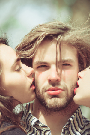 man with beard or bearded macho getting kiss by two pretty women or cute girls on sunny day on natural background. Love triangle. Relationship