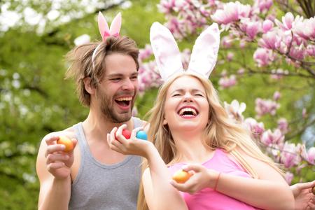 lapin sexy: homme et fille souriante ou jolie femme avec des oreilles de lapin tenant des oeufs colorés sur l'environnement floral. Bonne petite amie et petit ami dans le jardin fleuri. Couple amoureux. Printemps. Pâques Banque d'images