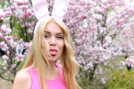 Spring, easter holidays celebration, Happy woman or pretty girl showing tongue, funny face grimace, in bunny ears on blond, long hair at trees with blossoming flowers in park on floral environment.