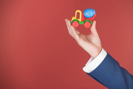 toy car truck in hand on red background, copy space Stok Fotoğraf