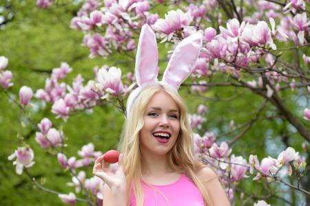 행복한 부활절. 행복 한 여자 또는 꽃가루 꽃에 꽃이 만발한 꽃과 목련 나무에서 붉은 계란을 웃 긴, 금발 머리에 장미 빛 된 토끼 귀에 예쁜 여자. 부활