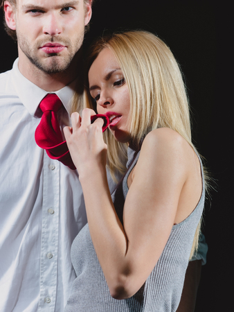 portrait of beautiful sexy couple in elegant shirt and red tie on black background Stock Photo