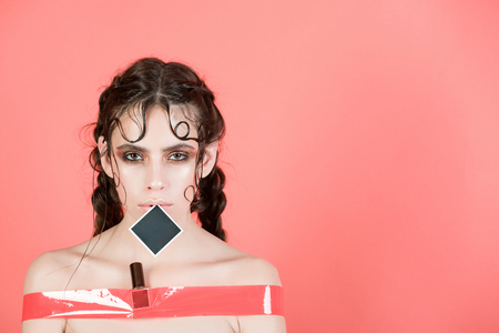 Cute girl or pretty woman with fashionable make up and hairstyle taped in rosy sticky tape with nail polish tube and black frame on lips on red background. Punishment. Restricted access, copy space