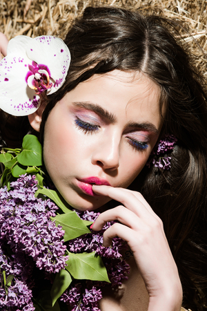 portrait of young woman or girl with beautiful lilac and orchid flower on haystack Stock fotó