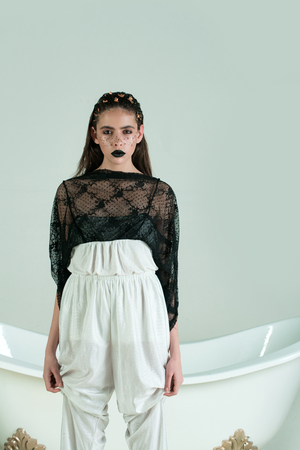 Pretty girl or cute woman with black lips, golden freckles, foil on face and hair, hairstyle wearing trousers and lace top at bath on white background. Creative makeup. Fashion. Sanitary, hygiene. Spa Banco de Imagens